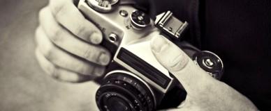 Мужчина держит в руках фотоаппарат
