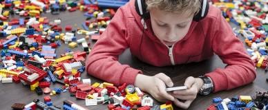 Ребенок в наушниках со смартфоном в руках
