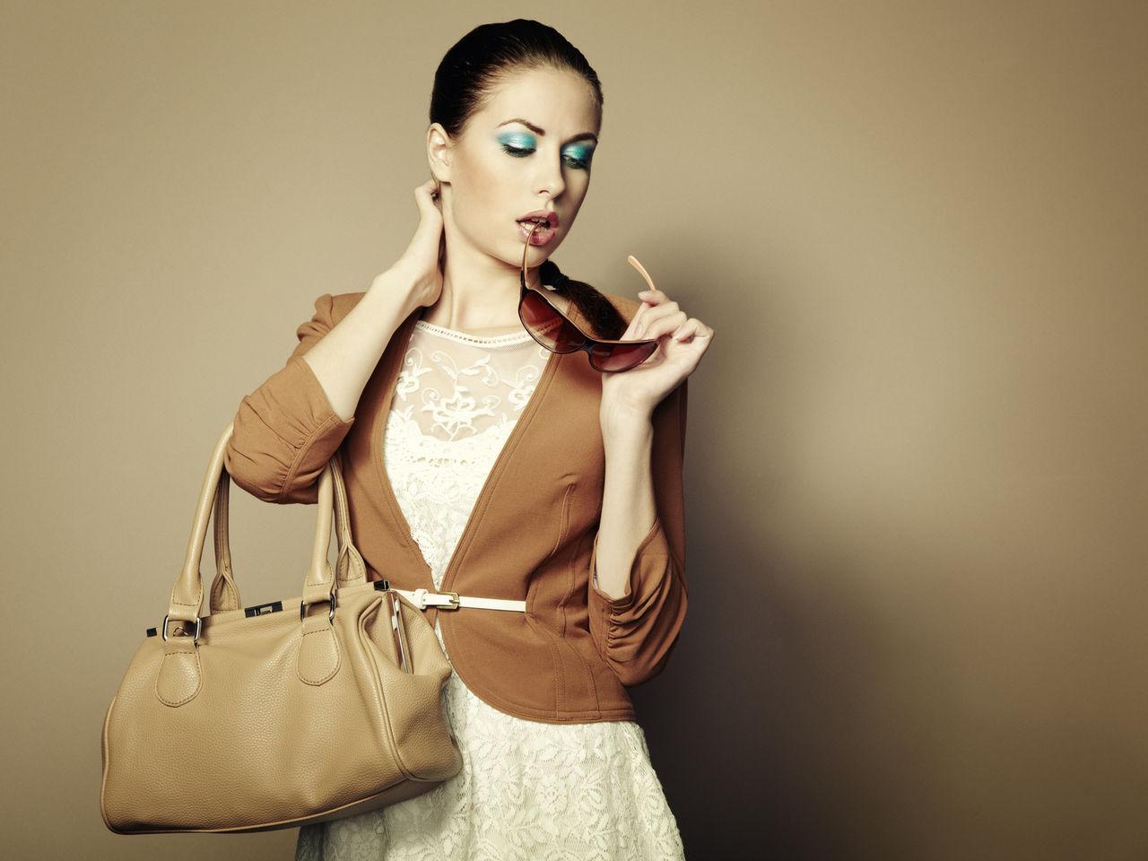 Девушка в белом платье из кружева и коричневом трикотажном жакете с сумкой и очками