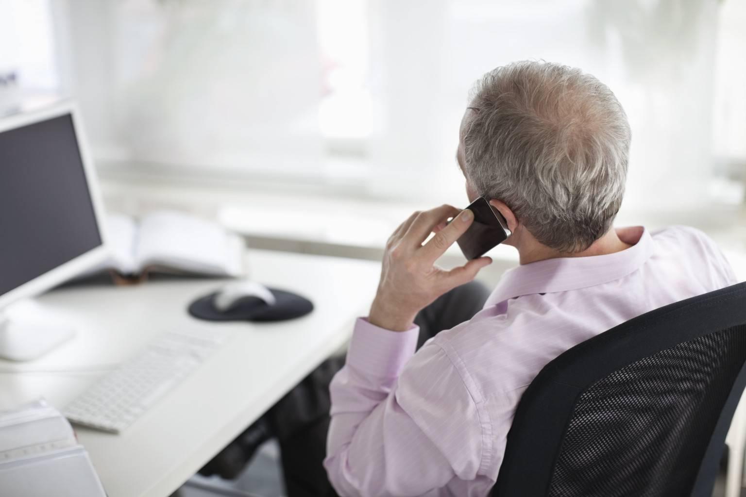 Мужчина сидит за рабочим столом с телефоном в руке